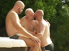 Three bear seasoned man-lovers kiss by pool