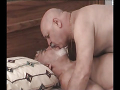 Fat silver homosexuals giving a kiss in bed